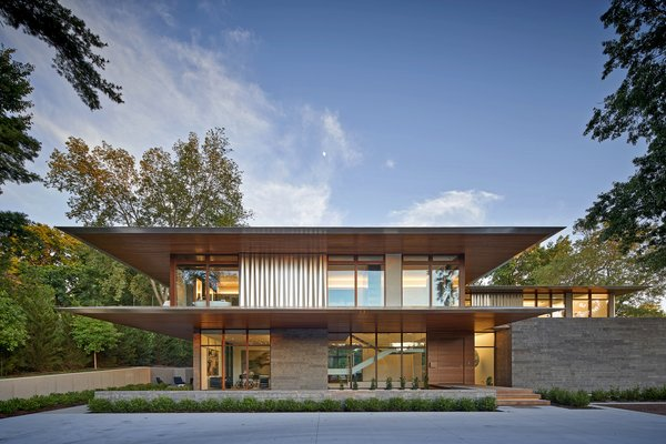 Dramatic in its horizontal expression, this private residence appears to extend into the landscape via deep overhangs and visual transparency.