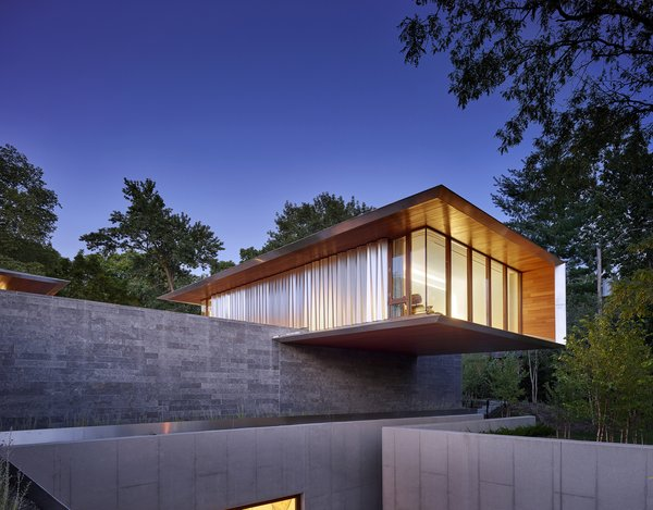 The second guest suite, clad in cedar and aluminum, extends over a horizontal limestone wall.