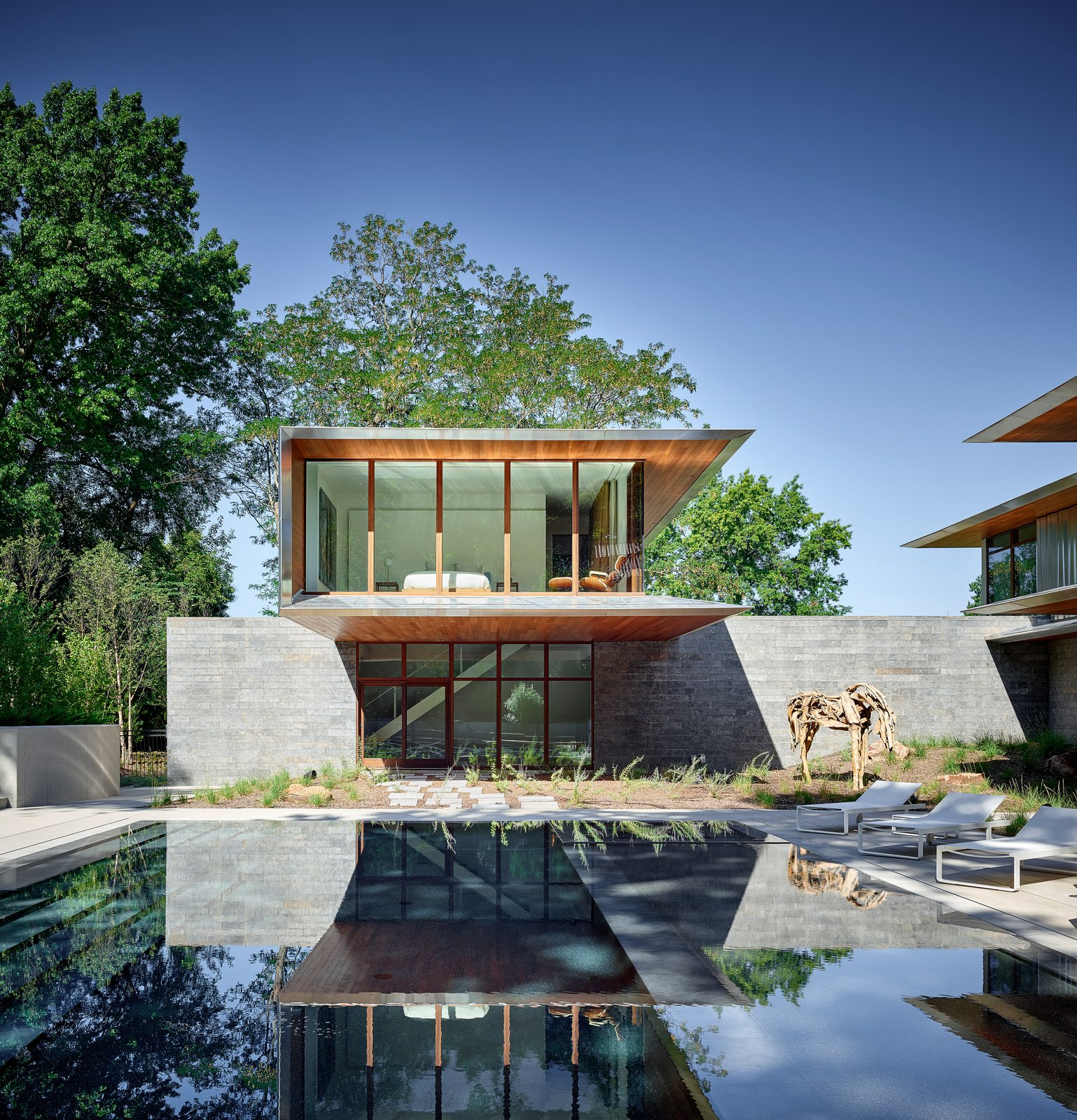 Outdoor, Stone Fences, Wall, Hardscapes, Trees, Swimming Pools, Tubs, Shower, Shrubs, Large Pools, Tubs, Shower, Back Yard, Concrete Patio, Porch, Deck, and Horizontal Fences, Wall One of the two guest suites dramatically cantilevers out over the pool.    Photo 5 of 23 in A Luminous, Eco-Friendly Abode Is Completed With its Own Modern Art Gallery from Artery House