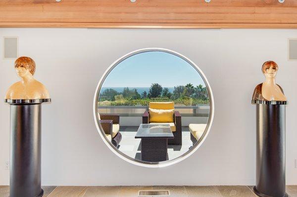 Dramatic windows—including circular shapes—frame scenic ocean views.
