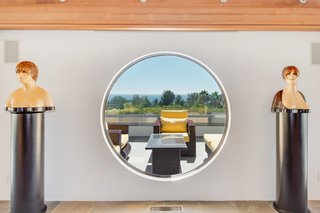 Dramatic windows—including circular shapes—frame scenic ocean views.