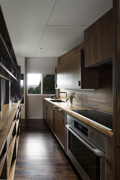 Dark brown wood contrasts with the bright, white wall and ceiling finishes. In the kitchen, modern appliances meet today's needs.