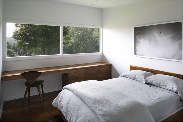 Wood built-in furnishings look onto the landscape from the bedroom.