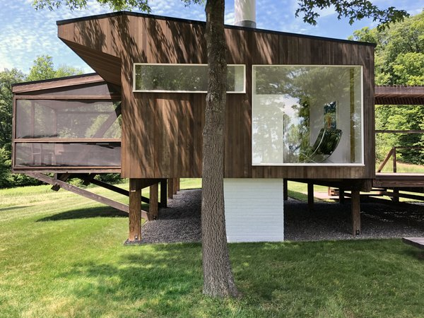 The structure appears to float above the ground. Wood stilts gently touch upon the earth, minimizing the building's footprint on the landscape. The brick chimney can be seen as it passes from the interior living spaces to the ground.