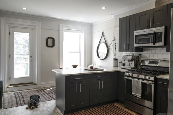 By painting the cabinets and installing a white tile backsplash, the designers were able to transform the kitchen into a modern cooking space without redoing the layout or the flooring.