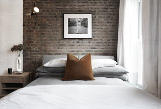 The master bedroom retains the original character of the home by maintaining the exposed brick, creating the illusion of a headboard.