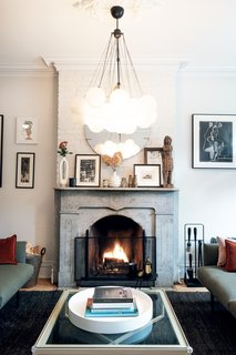 The designers were able to retain the existing fireplace, making it a beautiful centerpiece of the living room. They painted the existing brick white, providing a neutral backdrop to the eclectic art collection and custom chandelier.