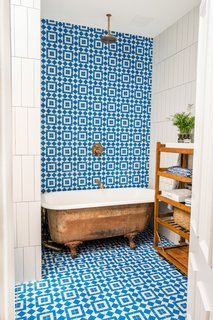 Colorful, patterned tile provides the perfect backdrop for the revamped clawfoot tub. Stewart-Schafer added new plumbing fixtures to make the tub double as a shower.