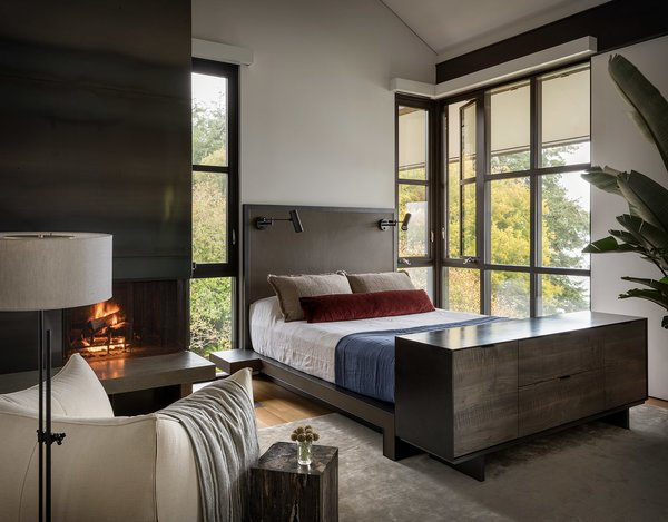 The master bedroom features a custom leather and steel bed, a collaboration by Geremia and fabricator Tod Von Mertens, and a rolled steel and Thassos marble fireplace.