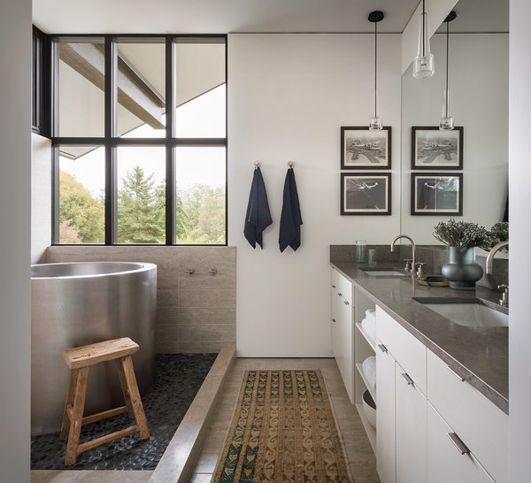 The bath areas continue the natural, simple material palette.  A large soaking tub sits atop pebble tile.