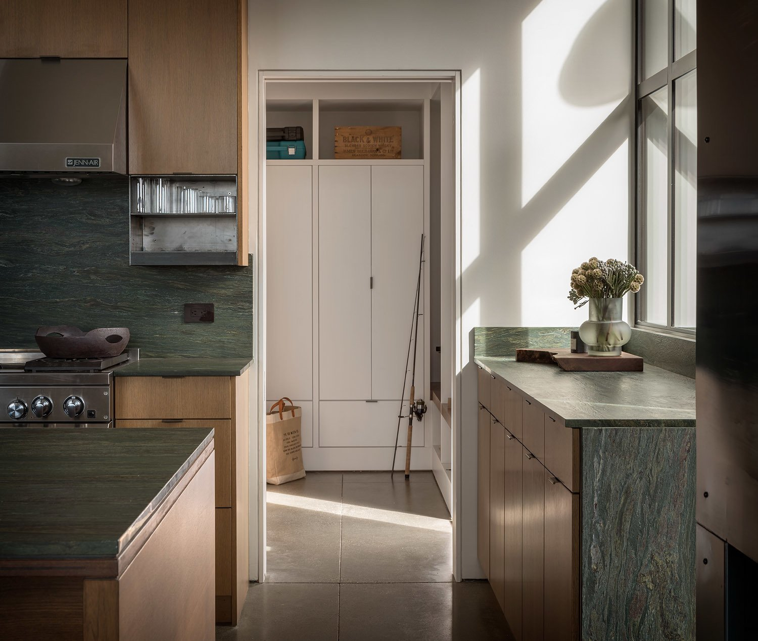 Kitchen, Concrete Floor, Stone Slab Backsplashe, Range, Range Hood, and Wood Cabinet The soapstone counters and back splash resonate with the natural setting, drawing in hues and colors from the surrounding landscape.   Best Photos from False Bay Home and Writer's Cabin