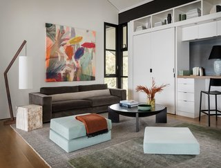 The open loft space above is filled with simple furnishings, colorful artwork, and rich textiles.