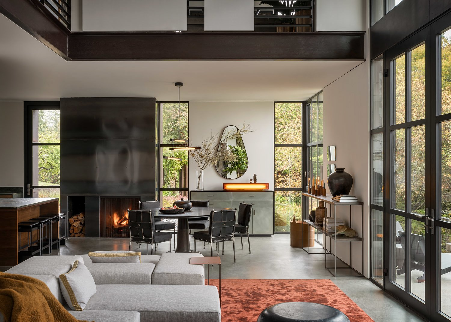 Dining, Rug, Chair, Ceiling, Standard Layout, Concrete, Accent, Wood Burning, Table, and Pendant A steel fireplace lies between the dining space and open kitchen.   Best Dining Accent Ceiling Pendant Photos from False Bay Home and Writer's Cabin