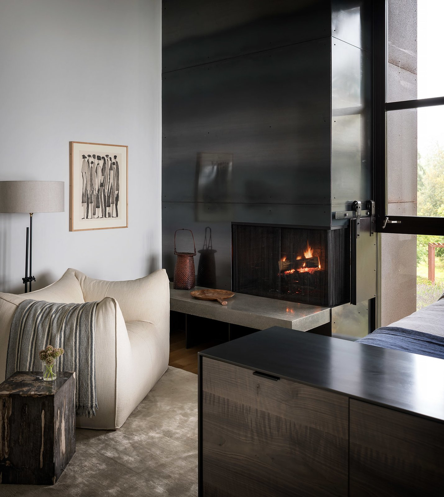 Bedroom, Chair, Storage, Bed, and Floor Lighting A vintage Pamono club chair sits next to the hearth of the fireplace.  Photo 18 of 20 in Geremia Design Imbues an Olson Kundig Retreat With Warm Tones and Modern Art from False Bay Home and Writer's Cabin