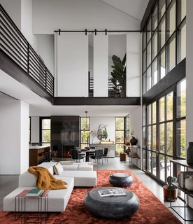 The upper floor wraps the main living space below, allowing for picturesque views from both levels of the home. Coffee bean tables by Holly Hunt sit atop a silk Tai Ping rust carpet, adjacent to a custom Living Divani Sofa.