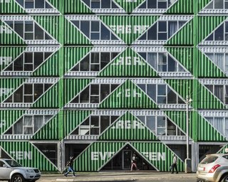 Diagonal cuts are mirrored across the facade, creating a rhythmic pattern of material and void.