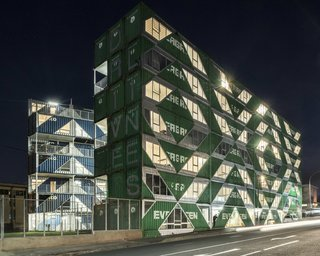 Large cuts in the outer walls of the shipping containers create a geometric pattern of glazed openings. At night, the openings create a patterned facade that is both solid and transparent.