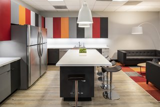 Pops of color carry through from the cabinets, to the carpet tiles, to the artwork and furnishings. Black and white accents balance with the boldness.