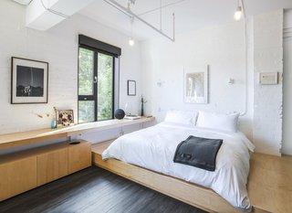 Minimalism and comfort blend to create a stylish, modern oasis.  Painted white brick walls, plywood built-ins, and simple lighting reflect the industrial character of the space in a new way.
