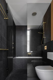 Large-format tiles, a glass-enclosed tub and shower combo, and elegant gold fixtures create a luxurious bath retreat.