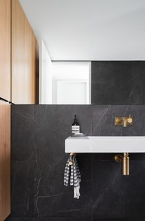 Minimal and sleek finishes decorate the bath interiors. Gold hardware is a rich element that pops against the dark tiled walls.