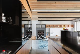 Continuously run wood slats visually connect the open living spaces while adding a warm, textural component. Black linear pendants are a contemporary way of introducing overhead light.