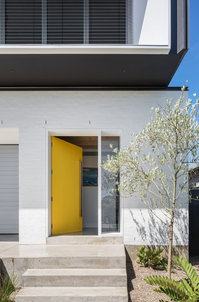 A bright yellow front door adds a bold pop of color to the minimal exterior palette.
