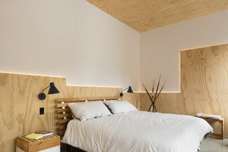 A geometric arrangement of back-lit plywood adds flair to a simple bedroom.