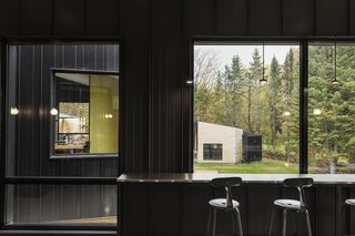 Built-in bar seating looks out upon the surrounding trees and into adjacent living spaces.