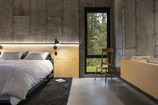 Concrete walls, a plywood ceiling, and built-in wood furnishings create sleek, minimal sleeping quarters. A plywood headboard is adorned with modern black sconces.