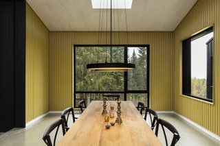 Yellow corrugated metal walls with grand glazed openings provide a bold space for dining in the trees.