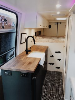 Located in the center of the van, the kitchen divides the sleeping space from the dining/work area.  A butcher block countertop, large farm-style sink, matte black faucet, and patterned floor tile provide a modern take on a galley kitchen.