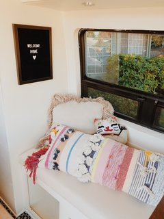 A lucky cat pillow from Urban Outfitters and a striped body pillow introduce color and personal style into the space.
