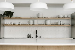 Modern white pendant lights from Schoolhouse hang above the open kitchen island. The geometric splash and open wood shelves continue into the kitchen.