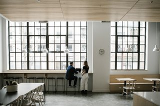Large, black-framed windows maintain the original character of the building while drawing in natural lighting. A custom built-in ledge and banquette provide alternative working seating in a collaborative environment.