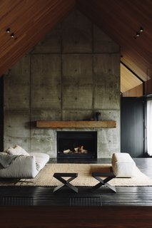 Concrete masses break up the grand interior spaces, while providing some solidity to the light framework of the home.