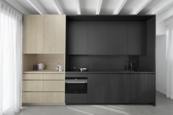 Natural and black painted oak cabinets provide plentiful storage in the galley kitchen.