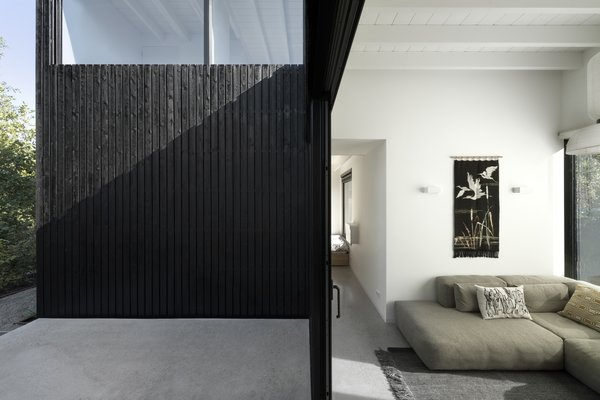 The darkly stained exterior contrasts with the white, light-filled interiors.