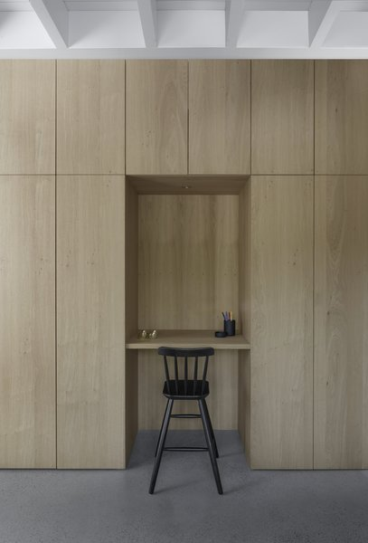 A recess in the floor to ceiling cabinetry provides a small working space.