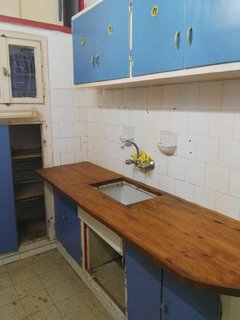 The original kitchen was cramped and outdated, with a single galley of cabinets and a small work surface.