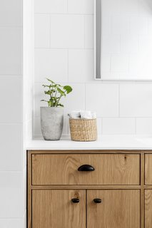 The bathroom features a blend of natural textures and clean lines.