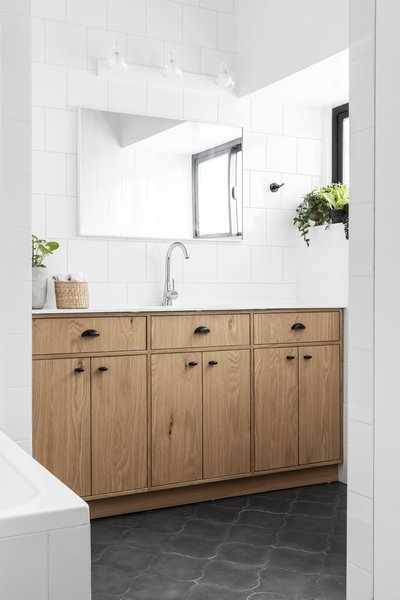 The totally reorganized bathroom includes a tub, a large vanity with storage, and elegant tiles.