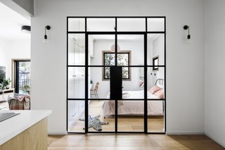 An iron-and-glass bedroom wall allows natural light to fill the kitchen and entryway.