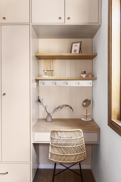 A built-in alcove provides a functional work surface and makeup area.