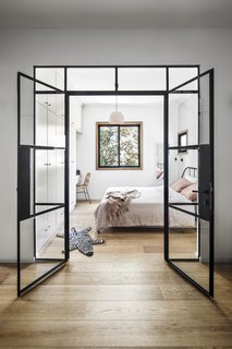 Daylight from the large bedroom window extends into the entry space, creating a warm, welcoming interior.