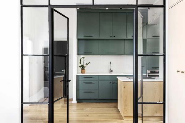 From the bedroom, glass and iron doors reveal the open kitchen space. Although unconventional for privacy, the glass doors enhance the feeling of an open plan.