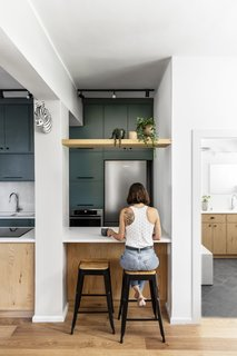"Dana Broza of Danka Design Studio was enchanted when she found this alluring bit of green in Tel Aviv's concrete jungle. Through unconventional space planning and creative design solutions, the designer completely transformed an outdated and dark midcentury apartment into a colorful and bright ""Urban Jungle."" In the kitchen, natural materials such as wood and rattan blend with pops of color. A simple overhang introduces additional seating at the counter."