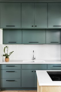 Grayish-green cabinets introduce one of the two main colors in the space. The white quartz countertop and backsplash provide a clean, minimal aesthetic.