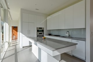Sleek, white custom cabinets quietly tie in with the original character of the home.