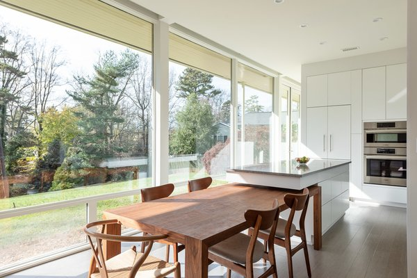 The uniquely designed kitchen island extends above the dining table to provide additional space for dining and cook prep. When not in use, the dining table can be pulled away, providing a freestanding island.
